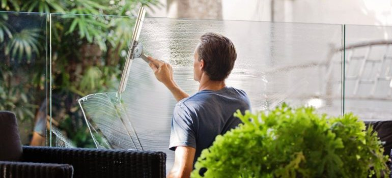 A man cleaning a glass wall - hiring professional cleaners will help you cope with moving stress