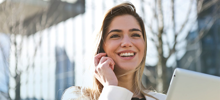 A woman speaking on the phone, smiling