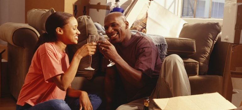 Couple making a toast, surrounded by moving boxes