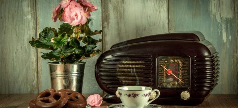 Vintage radio and pot of flowers behind a cup of coffee and plate of cookies