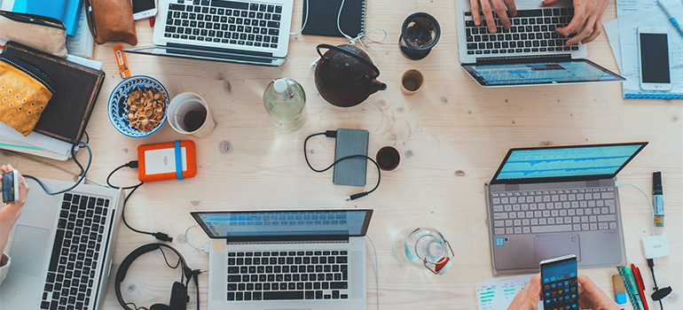 A table filled with working laptops, mobile phones, coffees, and office supplies