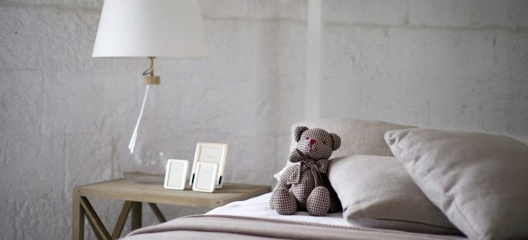 A grey bed with a teddy bear on it.