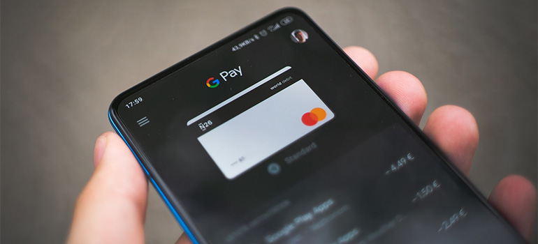 A person holding a smarphone with a google pay option open