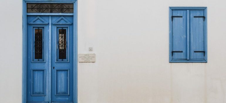 A white wall with a blue window and a door.