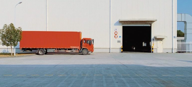 red truck parked in front of a white warehouse