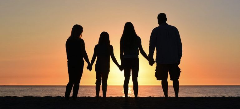 a family holding hands looking at the sunet