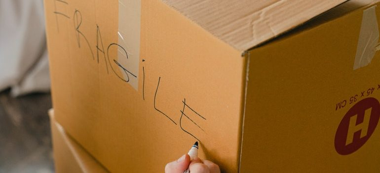 """Person writing """"fragile"""" on a box."""