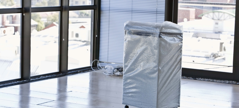 A mobile air condition covered by bubble plastic