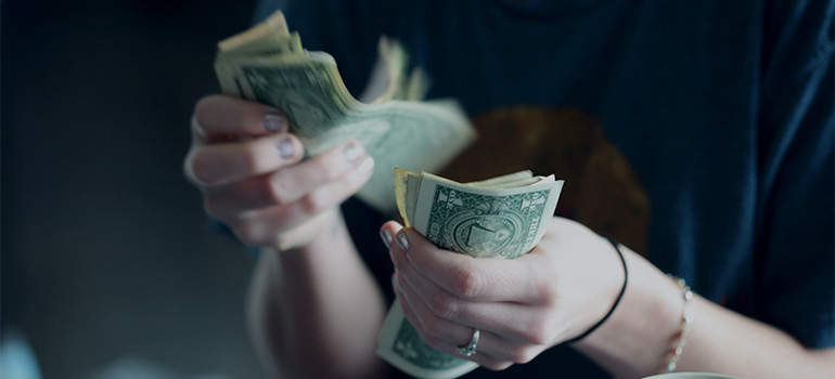 A girl counting money with the goal of reducing relocation expenses