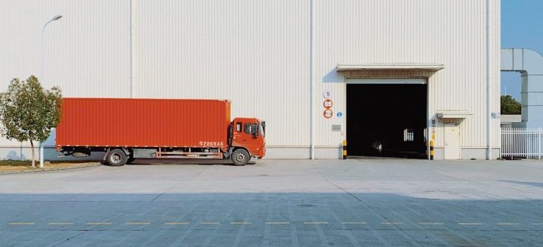 red truck outside of a white warehouse