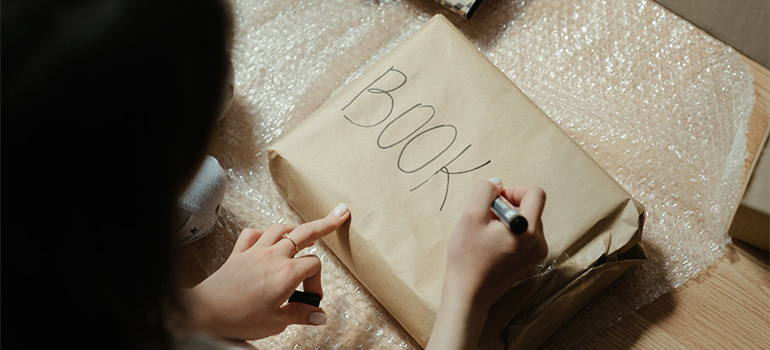 A woman labeling a package