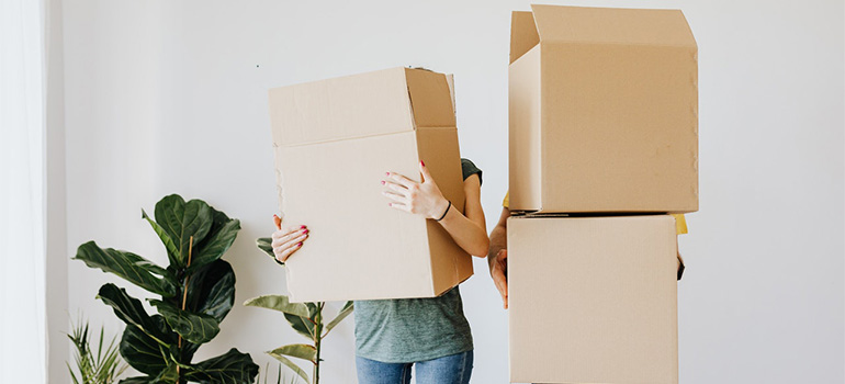 Two people holding boxes