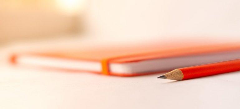 An orange notepad and an orange pen.