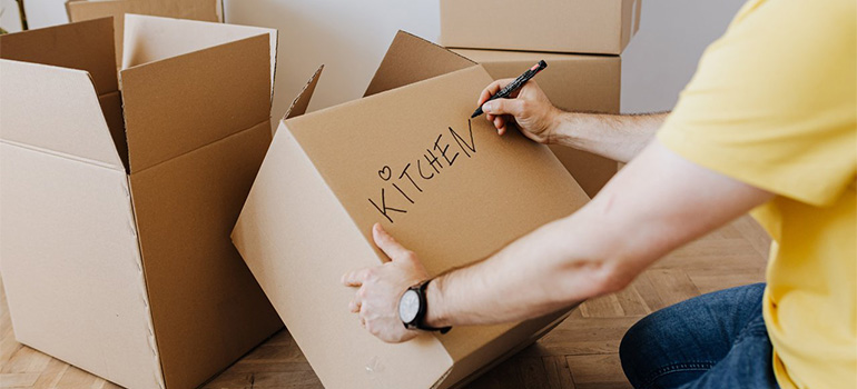 A man labeling his boxes