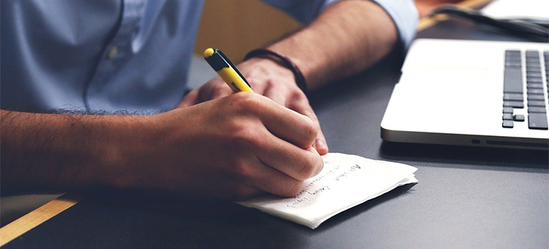 A man writing his DIY moving plans