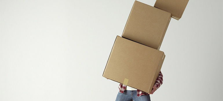 a man carrying boxes as one of mistakes when storing fragile items