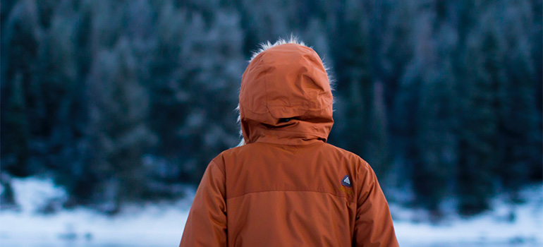 A person in a winter jacket, standing in front of a forest