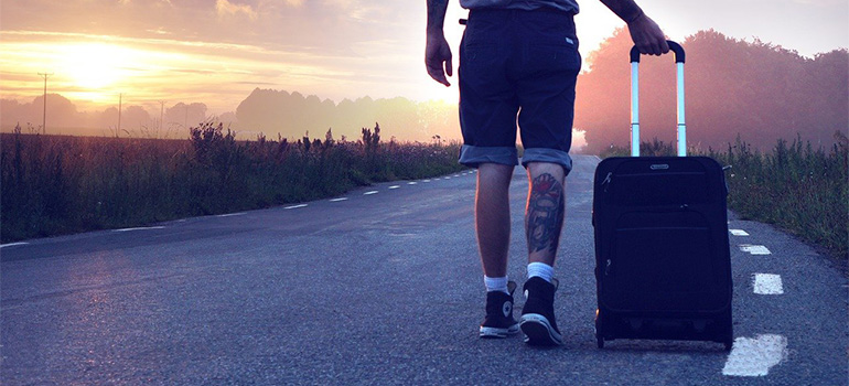 A man with a suitcase, trying to move abroad on a budget