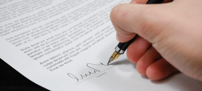 Person signing a contract after dispelling misconceptions about self storage.