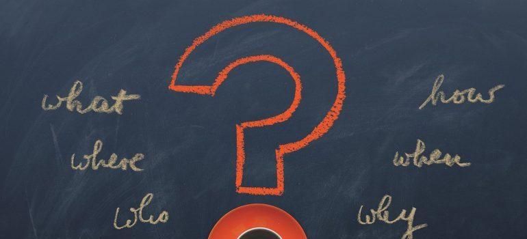 A question mark and words written on a blackboard.