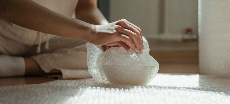 A woman packing a vase in bubble wrap