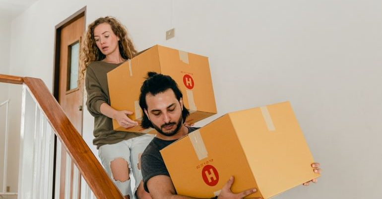 A couple, carrying boxes down stairs.
