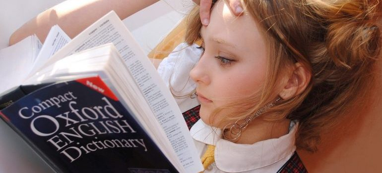 A girl reading a dictionary while trying to prevent one of the most common issues with global moves.