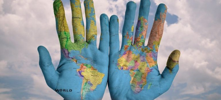 Hands on which a map of the world is painted.