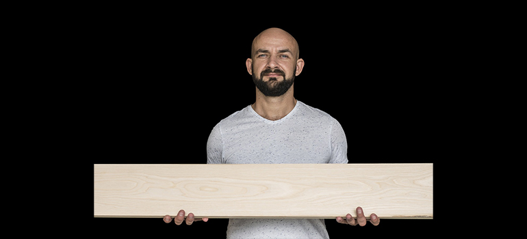 a man carrying a wooden board