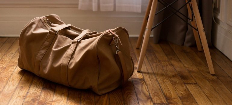 A brown bag next to a chair in which to pack an essentials box when moving.