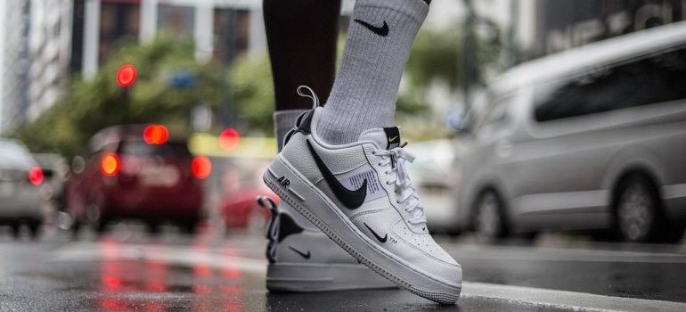 A person wearing white Nike sneakers that help you stay safe during your moving day.