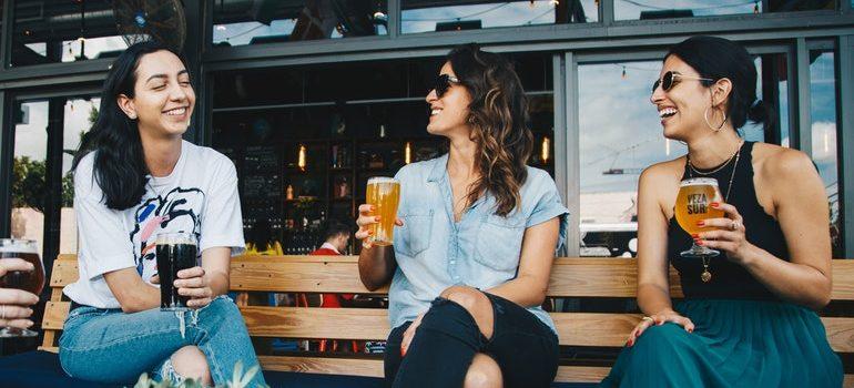 Three women drinking cocktails.