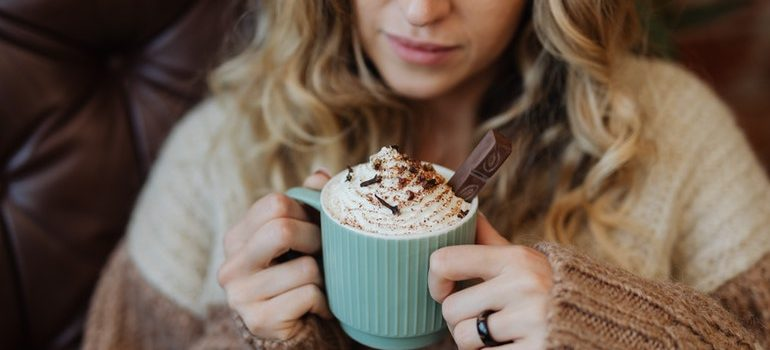 Person drinking hot chocolate to enjoy winters in Seattle.