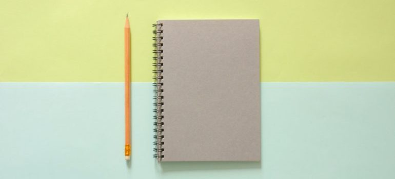 A notebook and a pen against a green and teal background.