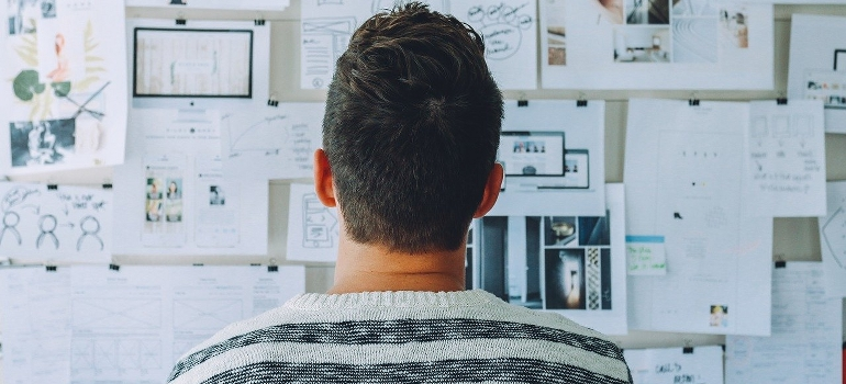 A man looking up on plans on a whiteboard.