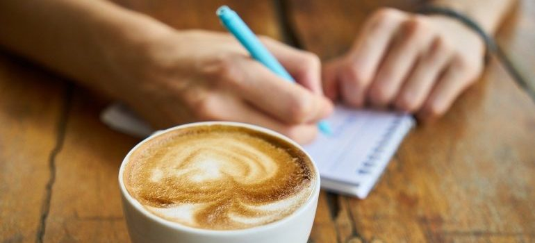 A cup of coffee and a person writing in a notepad in order to give your movers feedback.