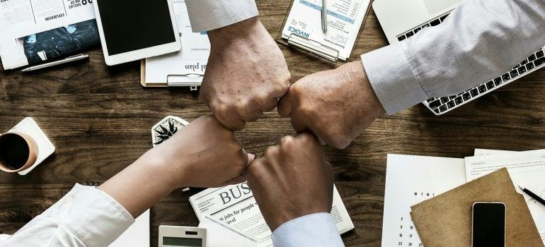 A group of people fist-bumping.