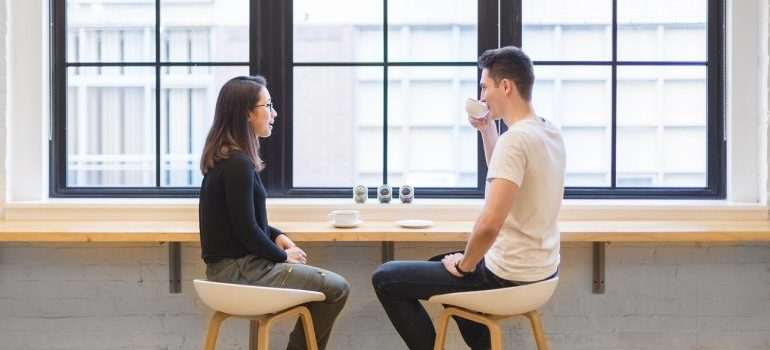 A man and a woman talking in a coffee shop.