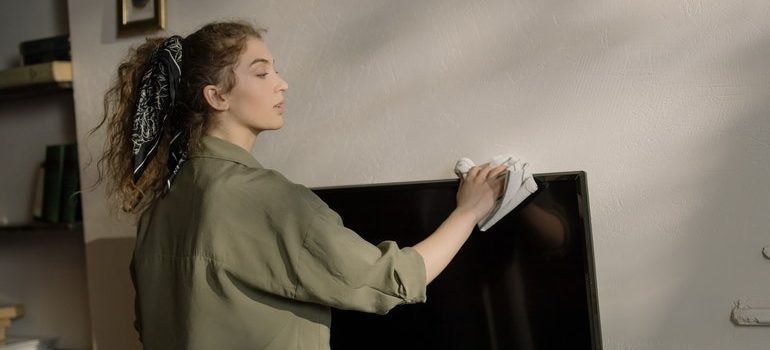 Person cleaning a TV screen to avoid mistakes when storing a flat screen TV