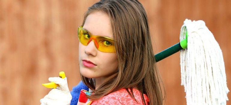 A girl holding a mop.