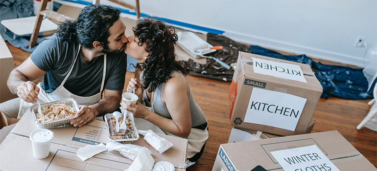 A couple eating takeout over unpacked boxes