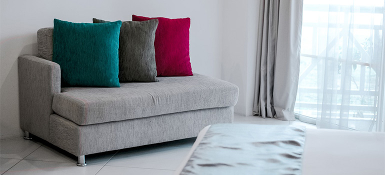 A gray couch with a blue, a gray and a red pillow on it in a well-lit room