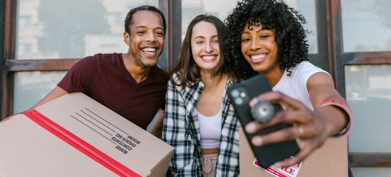 three people carrying moving boxes, taking a selfie