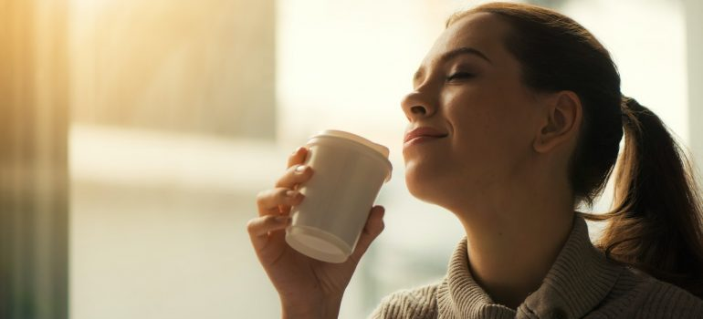 A woman drinking coffee preparing for a moving day.