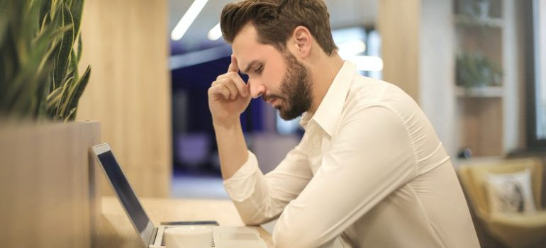 A man looking at a laptop screen and thinking.