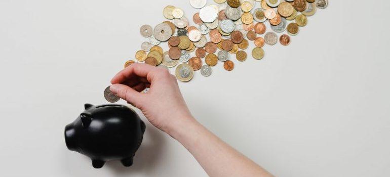 person depositing a coin into a piggy bank