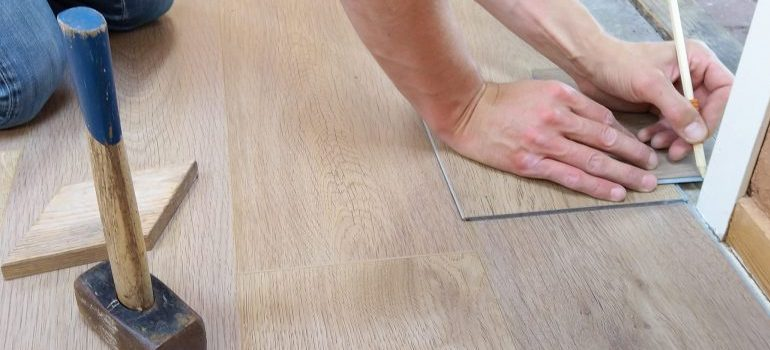 buying a fixer upper in Seattle - man working on flooring