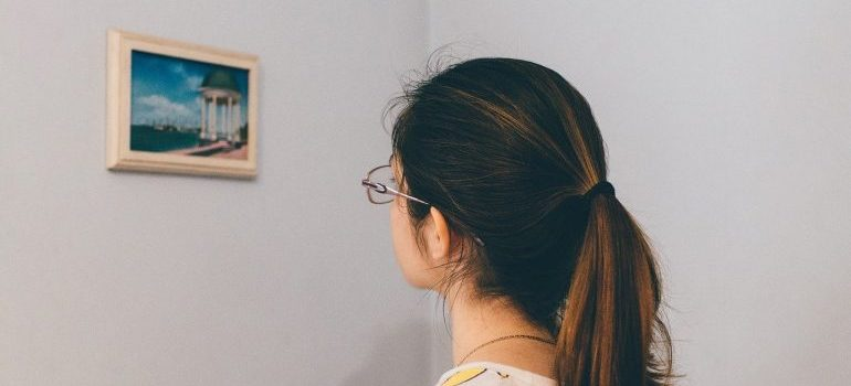 A woman looking at a picture on the wall.