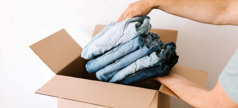 Person packing jeans in moving boxes