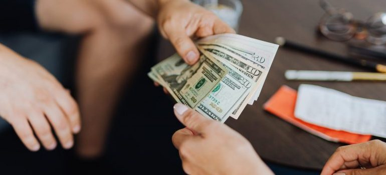person handing money to another person